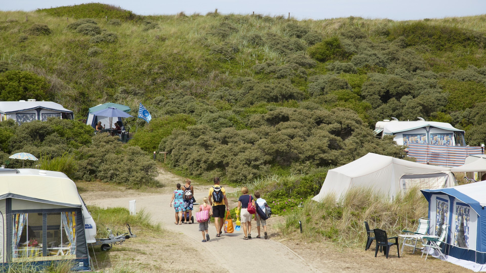 Groep loopt richting strand op Camping Kogerstrand VVV Texel