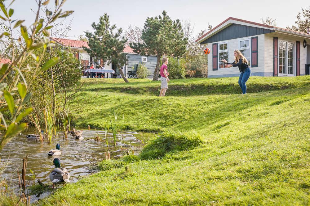Moeder en kind spelen voor vakantiewoning Vakantiepark De Krim VVV Texel