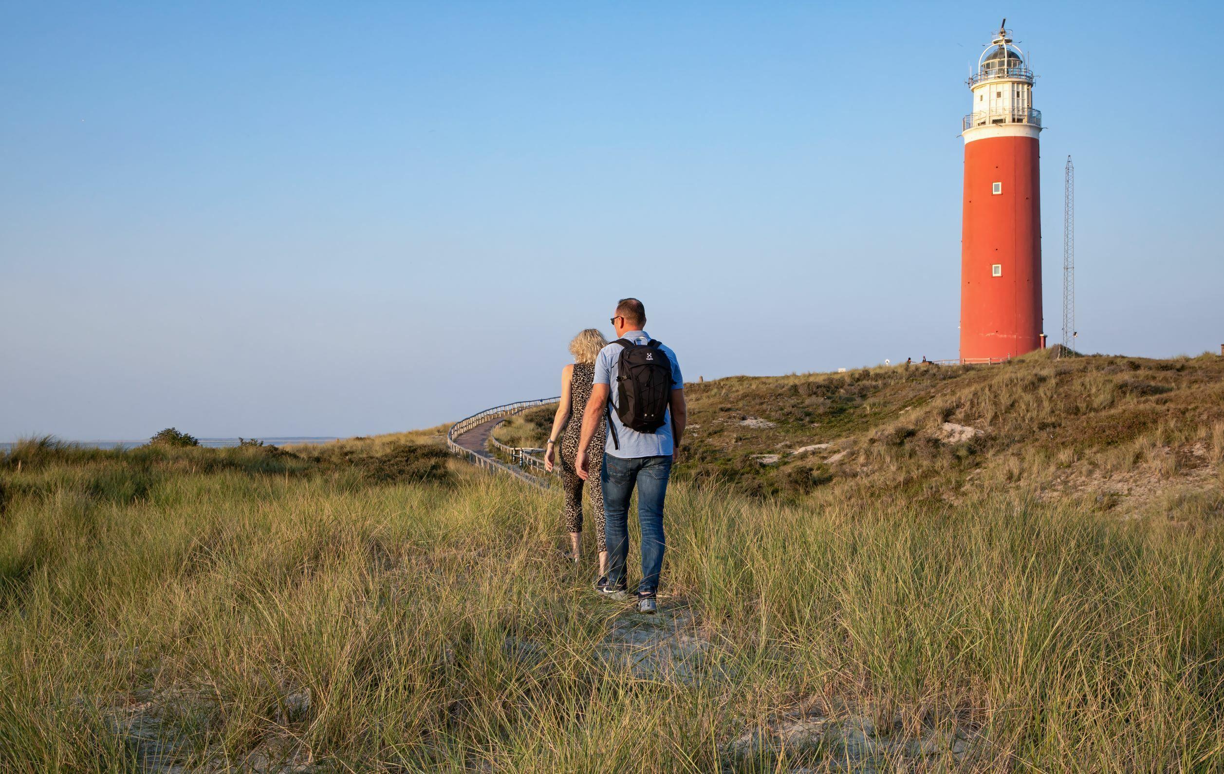 Stel wandelt door de duinen bij de vuurtoren VVV Texel Fotograaf Justin Sinner