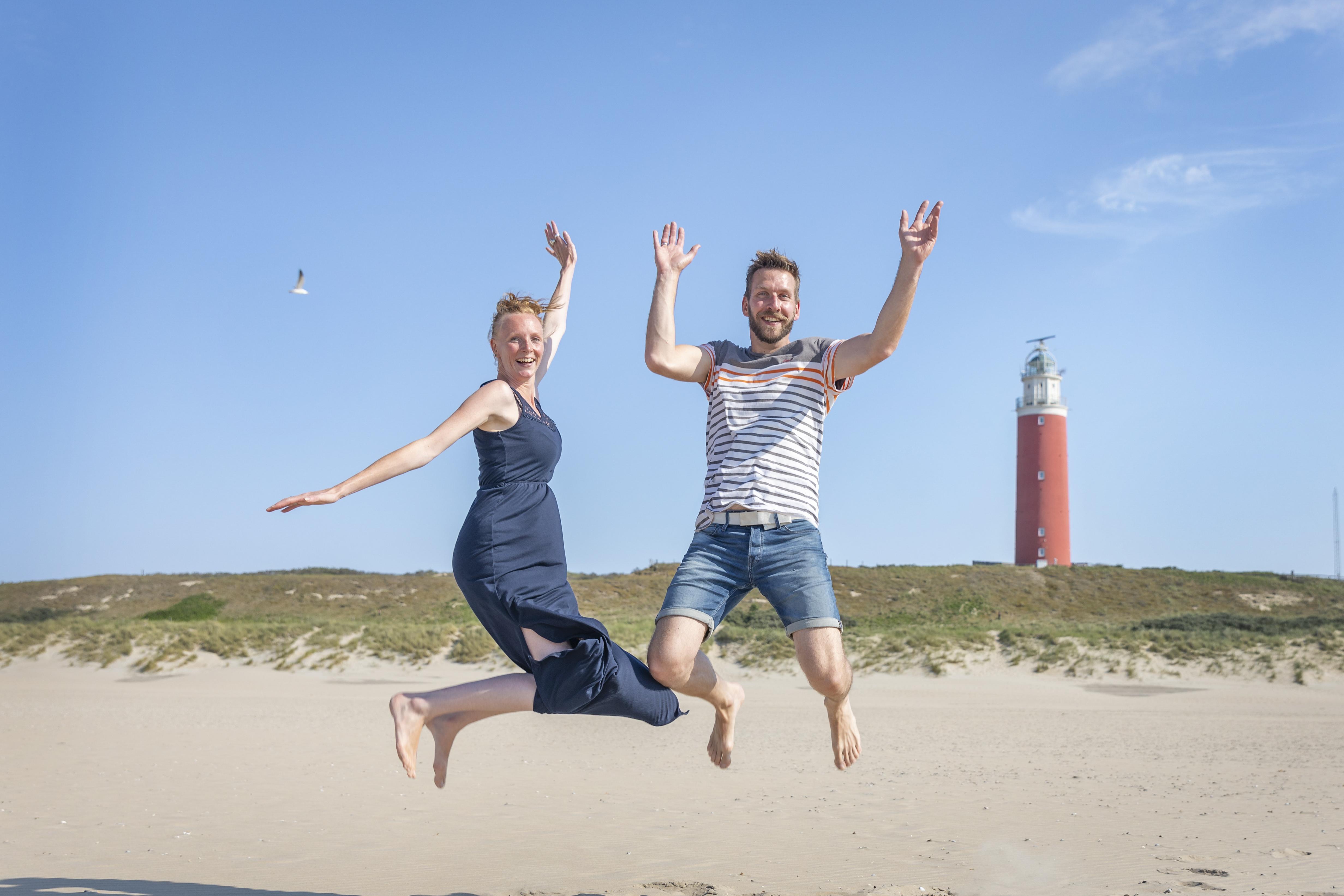 Stel springt in de lucht bij de vuurtoren VVV Texel Fotograaf Evalien Weterings